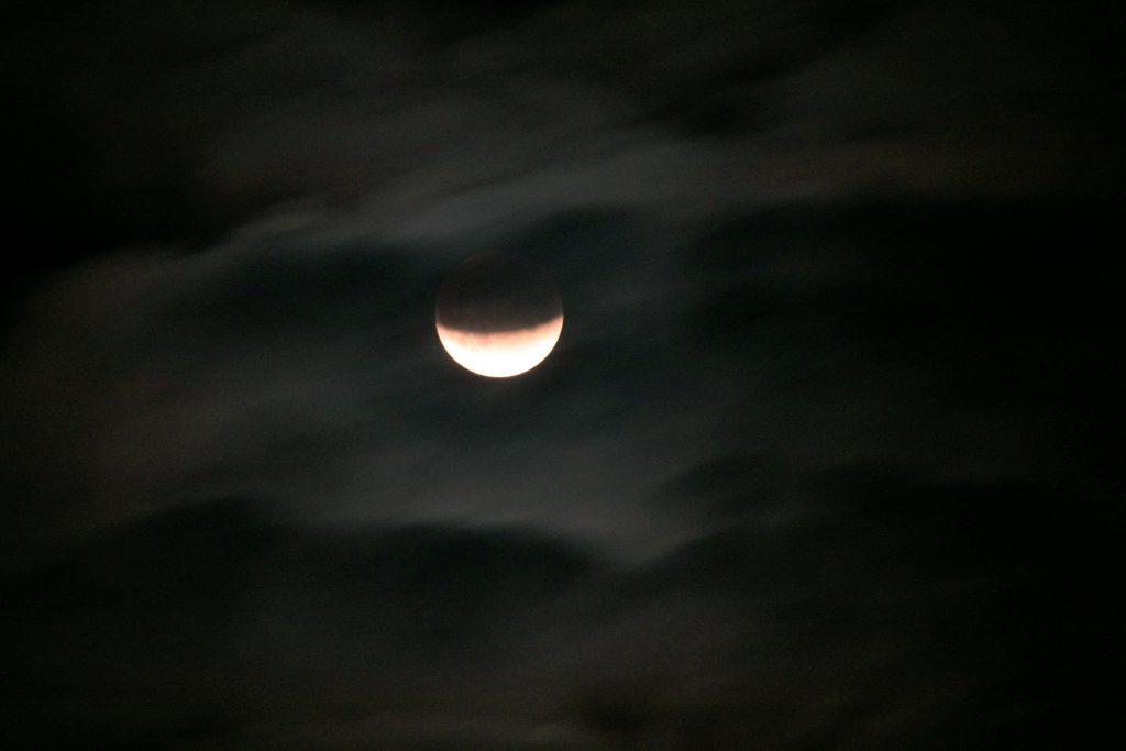 Partielle Mondfinsternis hinter Wolkenschleiern